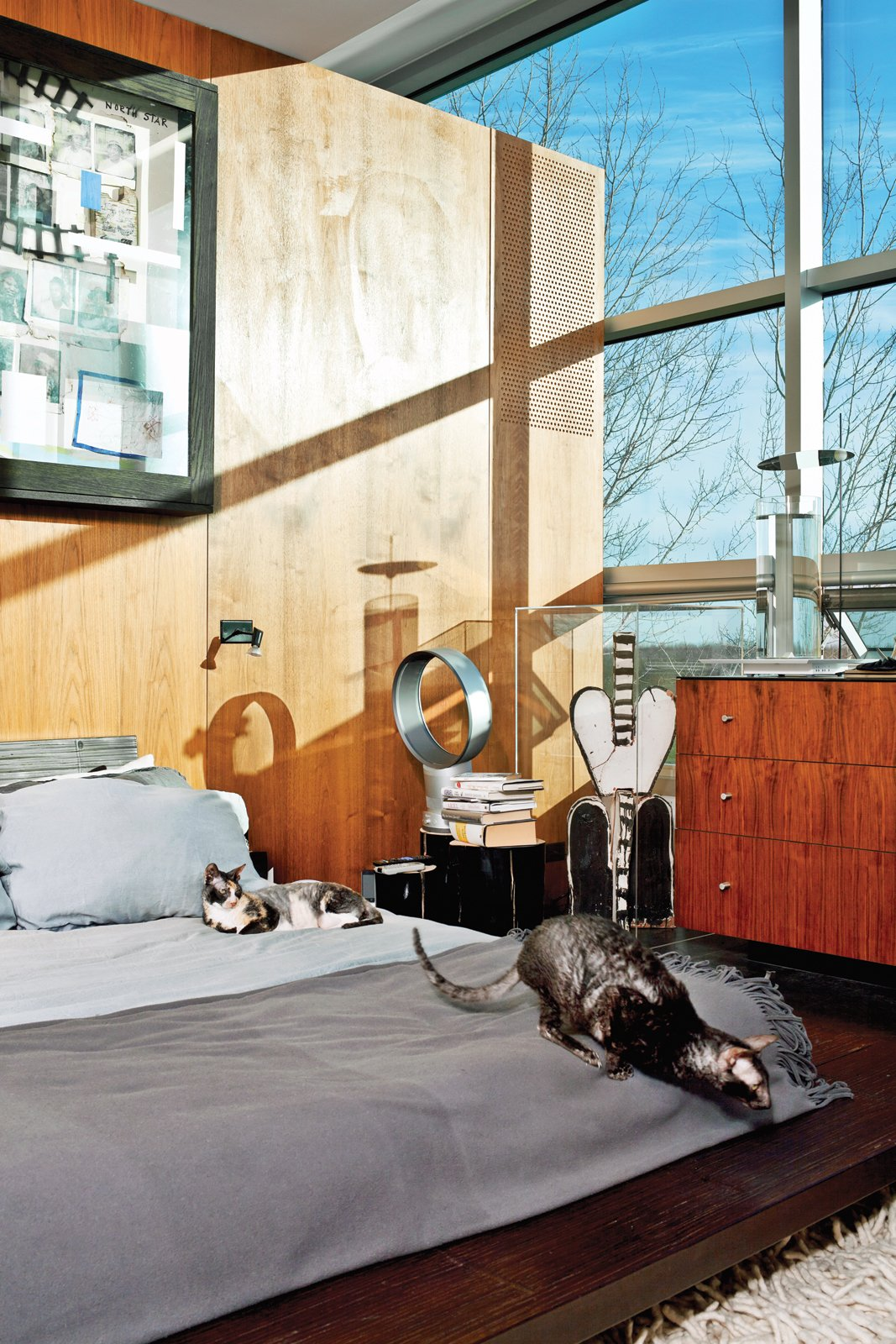 The master bedroom; the painting is by Radcliffe Bailey. Tagged: Bedroom, Dresser, Bed, Dark Hardwood Floor, and Rug Floor.  Photo 1 of 21 in 21 Cats Living in the Modern World from An Architect References Local Architecture to Build a Modern Home