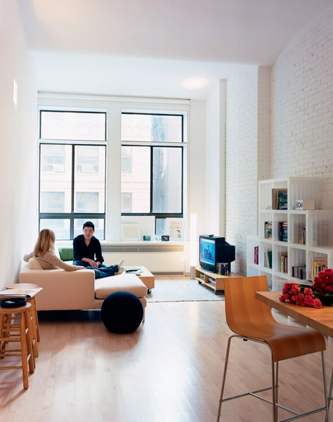 "A reflective light shelf sits atop the lower window units. ""When light hits the shelf, it reflects back on the ceiling,"" Woo explains. ""This is a very deep space, so we tried to bring the light as far back as possible."" The Neo sectional chaise by Niels Bendsten provides comfortable seating for Wonbo and his friend Alyssa Litoff. The Cubits shelves are by Doron Lachish."