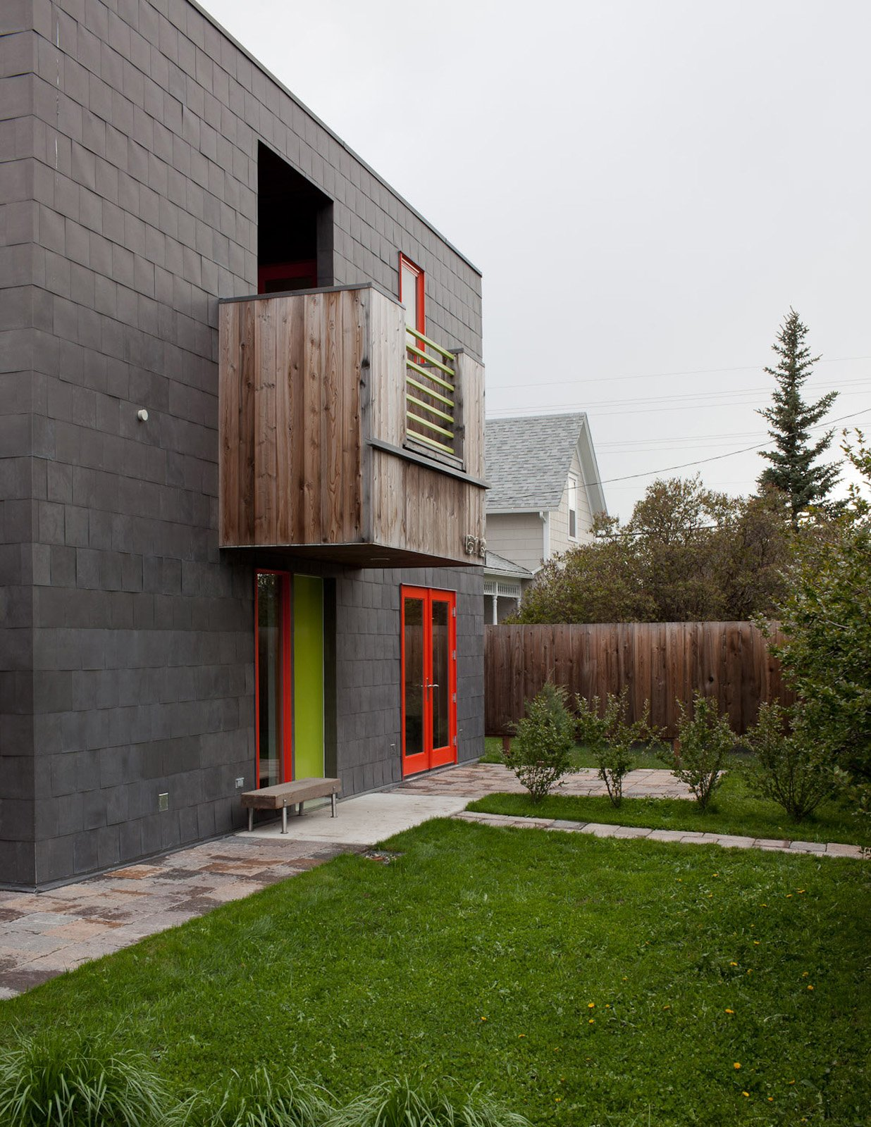 A handful of boxy protrusions on the facade give the modernist residence an additional three-dimensionality. The colorful window frames and door also give variety and depth to the gray structure. Tagged: Exterior and House.  Photo 10 of 16 in A Sound Professional Goes DIY While Building an Affordable Montana Home