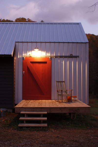 The red barn door on a sliding track door is an icon, built from salvaged pine from the original farmhouse. Image courtesy Chad Everhart Architect.