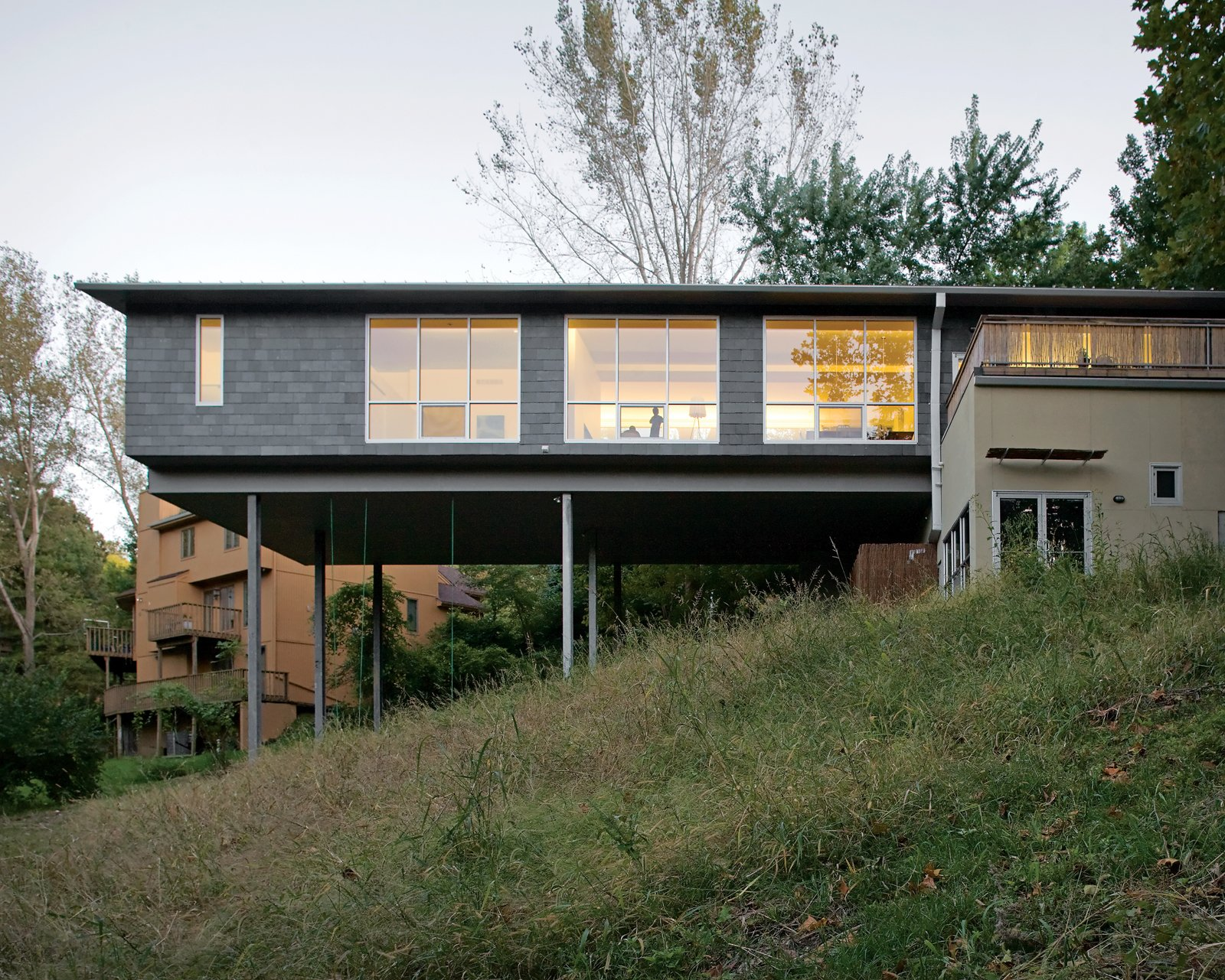 The Arnolds' bedroom and living area float over the hillside, the large windows allowing light to flood in from both sides. A bamboo-enclosed deck sits atop the house's foundation.  Daring Hillside Homes by Diana Budds from A Lot to Love