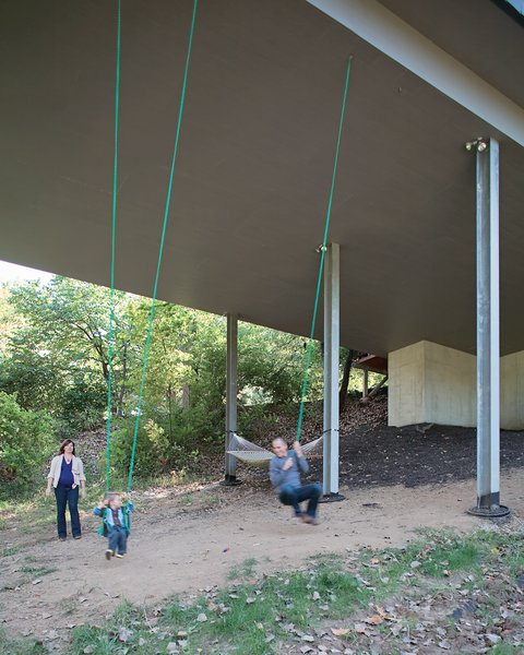 Julie, James, and Christian enjoy an unexpected bonus of living in a house on stilts—–a pair of swings suspended from the base of the structure. The family often goes for walks on the property, looking for wildlife and playing in the tepee they built in a secluded space in the woods.