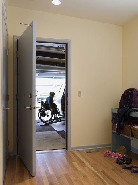 """The architects created a mudroom off the garage with plenty of room for quick turnarounds and busy family comings and goings. Much of the garage had been taken up by a large ramp before the concrete floor was repoured on a slope that meets with the house, eliminating the need for a more cumbersome ramp and allowing room for storage shelves. """"Your home is a place where you shouldn't have to put out too much effort, whether you're a person with a disability or not,"""" says Braitmayer. """"You should be able to reserve all that energy and effort for the outside world."""""""