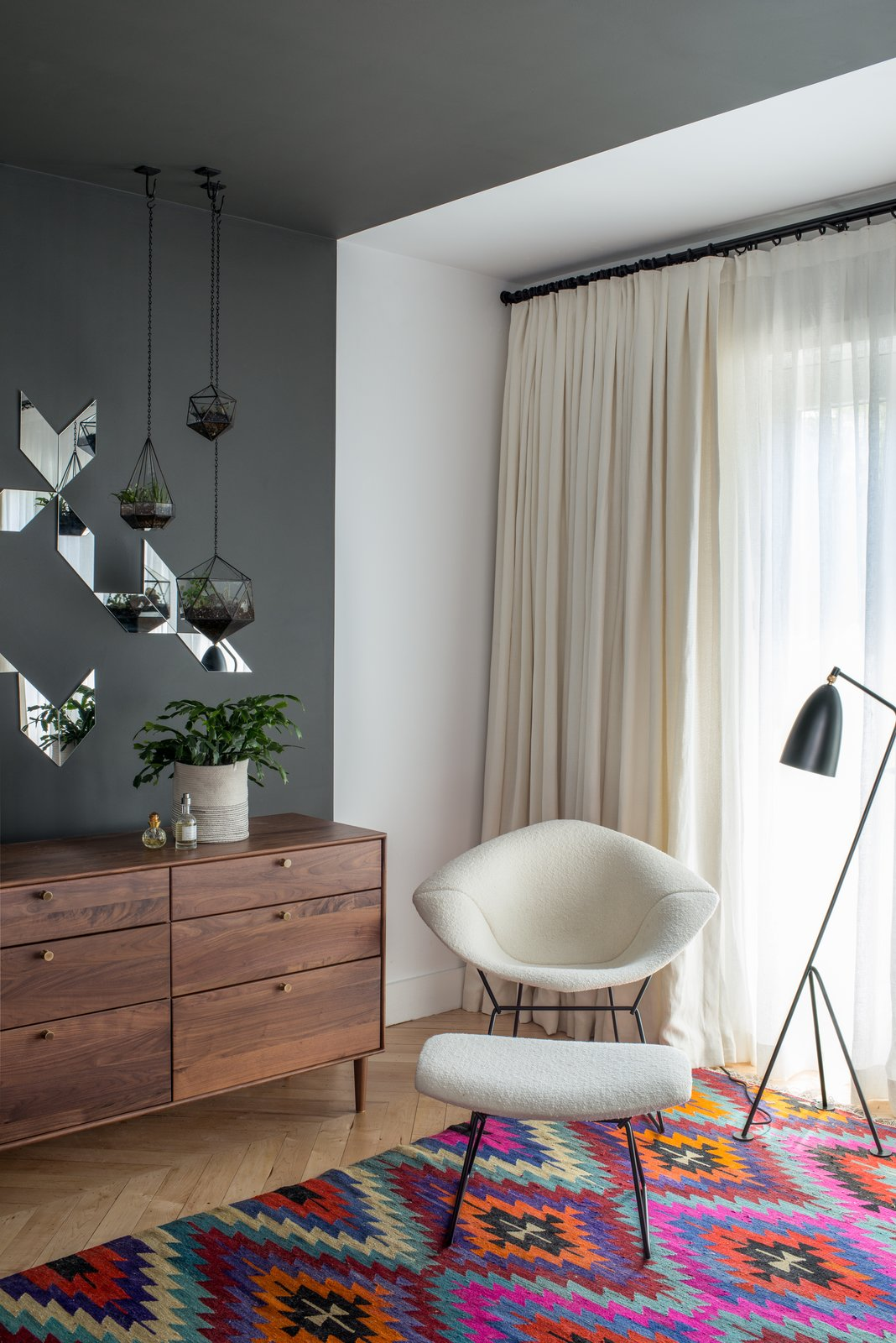 """In a corner of the master bedrooms, a black Greta Grossman Grasshopper lamp sits next to a Bertoia Diamond chair with matching ottoman. Lead designer Chelsie Lee says the Turkish kilim was """"a lucky vintage find."""" A custom Jessica Helgerson cut mirror design is set off by hanging terrariums, made in Vancouver Score + Solder. The American Modern dresser in walnut is from Design Within Reach.  Photo 3 of 8 in Design Icon: Greta Grossman from Design Classic: Bertoia Seating Collection"""
