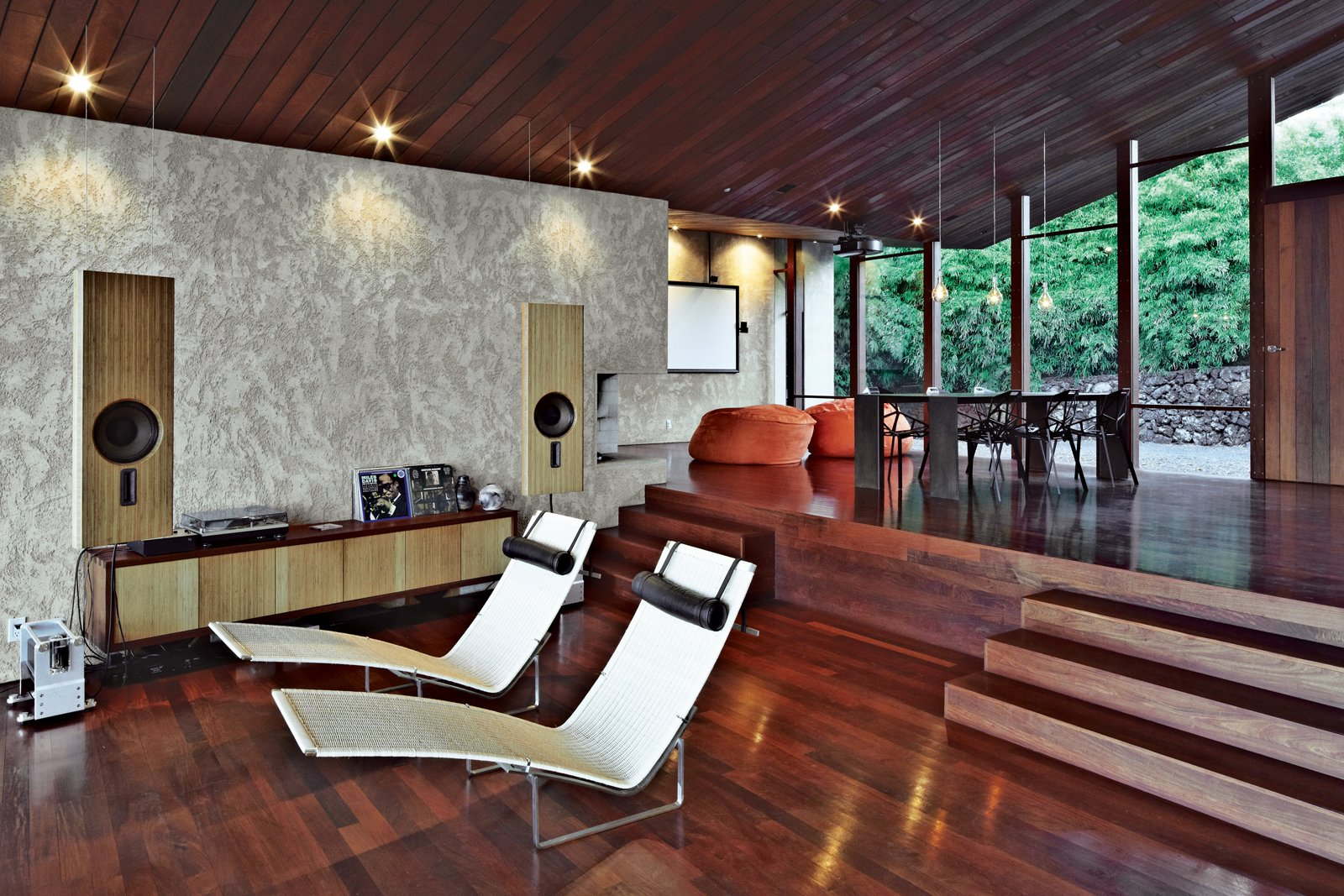 Dekleva Gregorič Arhitekti, along with resident Robert Stroj, designed most of the furnishings in the house, including the speakers, wall cabinet, and dining table. The beanbag pouffes are by Slacker Sack and the Chair-One dining chairs are by Konstantin Grcic for Magis. The stucco used on the walls was custom made from a mixture of white concrete, coral sand, dune sand, and lime. Tagged: Living Room, Chair, Recliner, Medium Hardwood Floor, and Ceiling Lighting.  Photo 3 of 10 in Clifftop House with Angled Roof in Maui