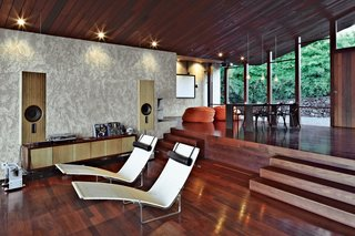 Clifftop House with Angled Roof in Maui - Photo 3 of 10 - Dekleva Gregorič Arhitekti, along with resident Robert Stroj, designed most of the furnishings in the house, including the speakers, wall cabinet, and dining table. The beanbag pouffes are by Slacker Sack and the Chair-One dining chairs are by Konstantin Grcic for Magis. The stucco used on the walls was custom made from a mixture of white concrete, coral sand, dune sand, and lime.