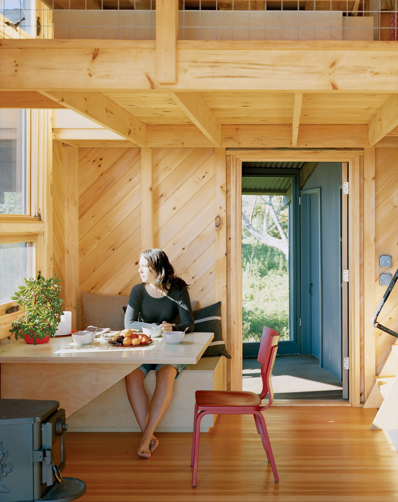 Alex enjoys a sun-filled breakfast at the built-in dining table and bench, one of many space-saving designs. Tagged: Dining Room and Table.  Photo 8 of 21 in A Tiny Cabin is This Writer's Off the Grid Getaway