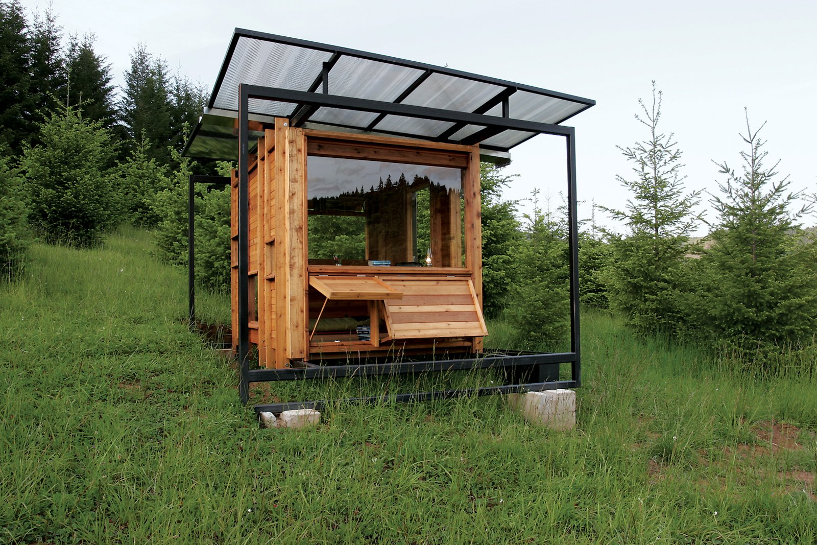 "Erin Moore of FLOAT Architectural Research and Design, based in Tucson, Arizona, designed a 70-square-foot writer's retreat in Wren, Oregon, for her mother, Kathleen Dean Moore, a nature writer and professor of philosophy at nearby Oregon State University. The elder Moore wanted a small studio in which to work and observe the delicate wetland ecosystem on the banks of the Marys River. Enlisting her daughter's design expertise, her professor husband's carpentry savoir faire, the aid of friends, and a front loader, Kathleen and her crew erected the structure in September 2007. Photo by Gary Tarleton. Totally off the grid—–Kathleen forgoes the computer and writes by hand when there—–the Watershed was designed to tread as lightly on the fragile ecosystem as the wild turkeys and Western pond turtles that live nearby. "" Tagged: Exterior, Cabin Building Type, Tiny Home Building Type, Wood Siding Material, Flat RoofLine, and Glass Siding Material.  Photo 98 of 101 in 101 Best Modern Cabins from Modern Off-the-Grid Retreat in Oregon"