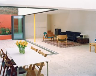 10 Indoor-Outdoor Homes in London - Photo 2 of 10 - The glass wall separating the main living area and the inner courtyard garden opens like an accordion to create a barrier-free transition. Built-in planters along the walls of the courtyard add greenery without eating into the valuable surface area of the courtyard.