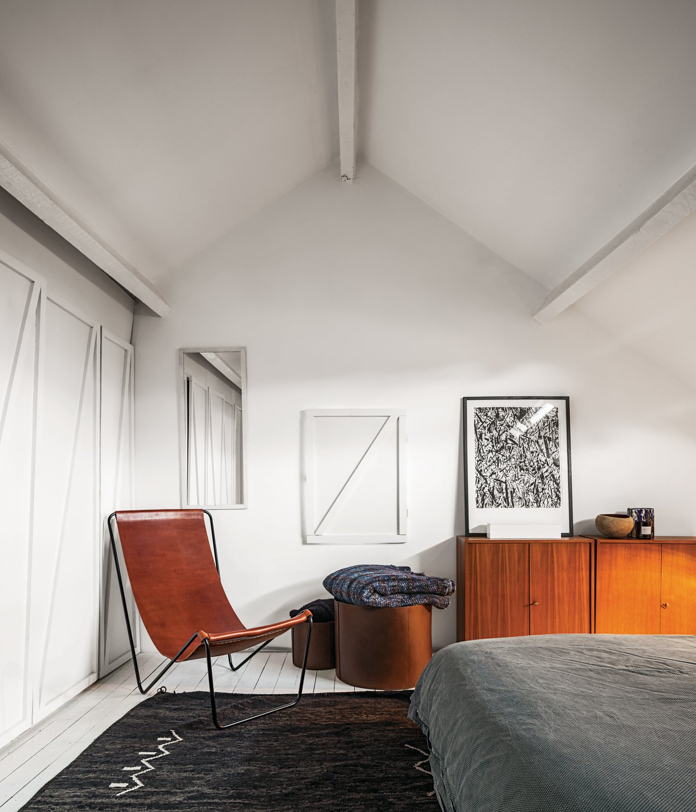 The pair painted the upstairs master bedroom white, and added a G55 sling chair and leather baskets from their recent design collections. The carpet is from a souk in Casablanca, and the bedcover is from Zara Home. Atop the vintage cup-board is an artwork by Vereecke's father. Verheyden incorporated all-new woodwork of his design into the room. Tagged: Bedroom, Chair, Bed, and Storage.  Bedroom by Lauren Gundlach from A Clever Belgian Couple Renovate Their Aging Brick Home