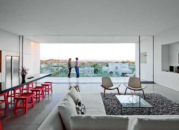 For the seating area, the couple selected a Charles sofa by Antonio Citterio for B&B Italia in addition to CH07 Shell chairs by Hans Wegner, a PK61 coffee table by Poul Kjærholm, and a Nesta rug from Design Within Reach. The dining table, an original design by Burnette, is surrounded by stools that belonged to a previous owner.