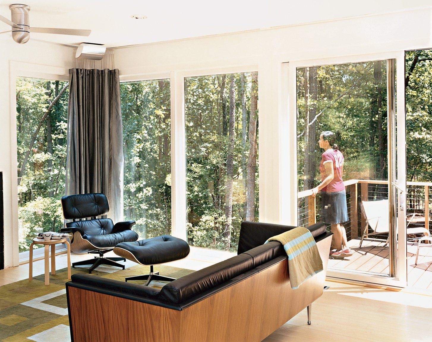 Tung takes in the wooded view from the house's back deck. Inside, the Goetz sofa, Eames lounge chair and ottoman, and Aalto stool are all from Herman Miller.The rug and throw are by Emma Gardner.  Photo 3 of 12 in Prefab, Proven
