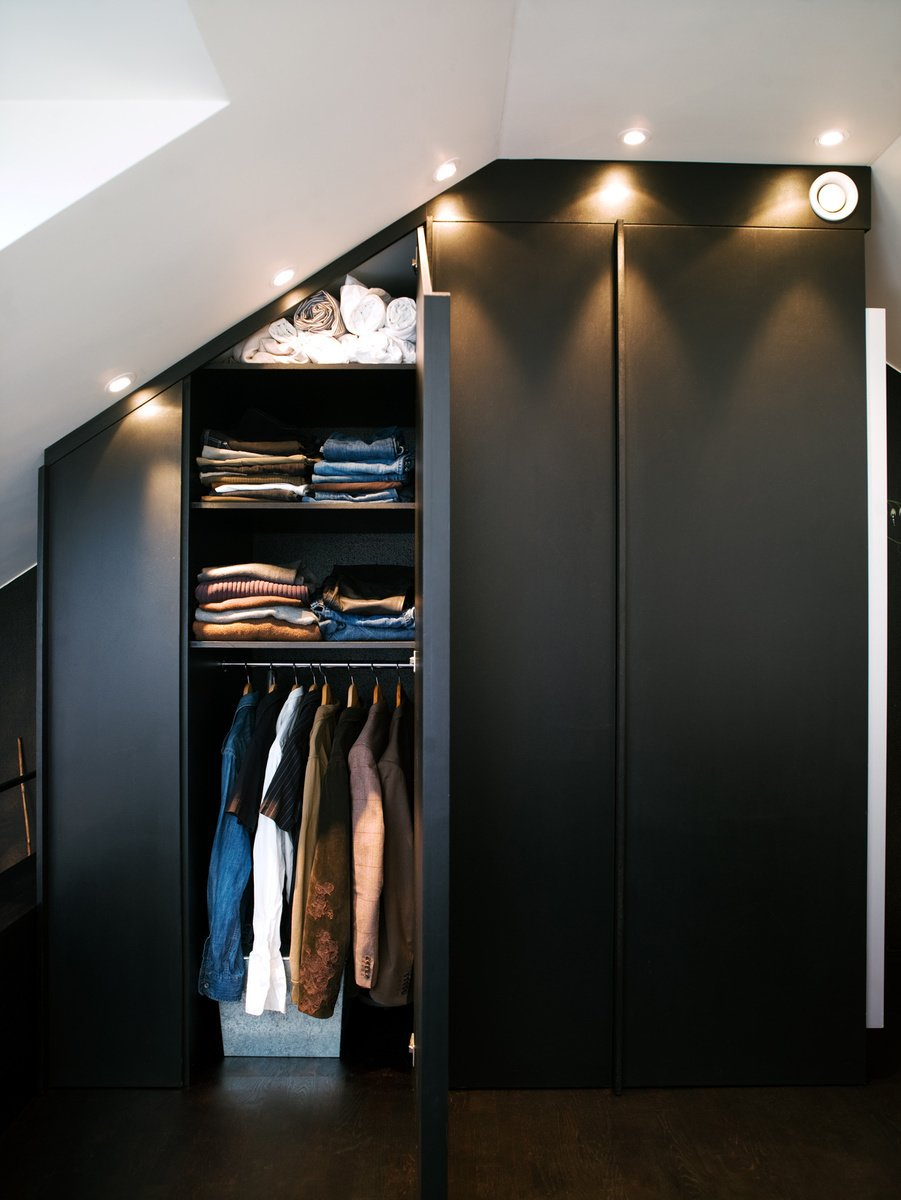 The apartment's built-in closets are deep and have mirrors on one side. Spotlights set flush overhead provide light and also allow the maximum amount of storage, all the way to the ceiling. For more of Schönning's dark, cozy-meets-modern interiors, visit his website. Photo by Per Magnus Persson. Tagged: Bedroom, Ceiling Lighting, Storage, and Wardrobe.  Storage by Dwell from Storage Solutions: 7 Hidden Closets