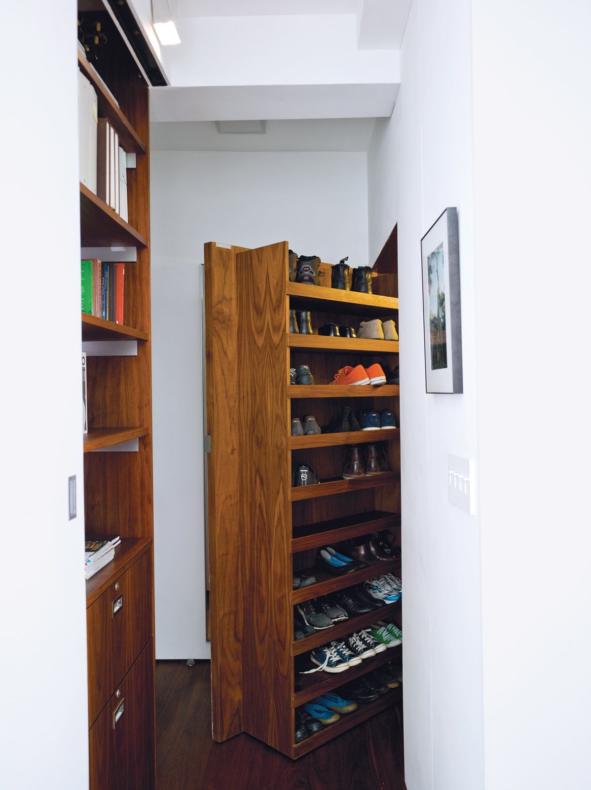 With space for shoes (the pair don't wear any in the home), Rollerblading gear, umbrellas, and more, the deep entrance closet helps the couple maintain their minimalist interior. A hanging rod, made by Specialty Lighting, has an integrated light that turns on when the 200-pound door is opened. specialtylighting.com  Photo 10 of 14 in Stow Aways