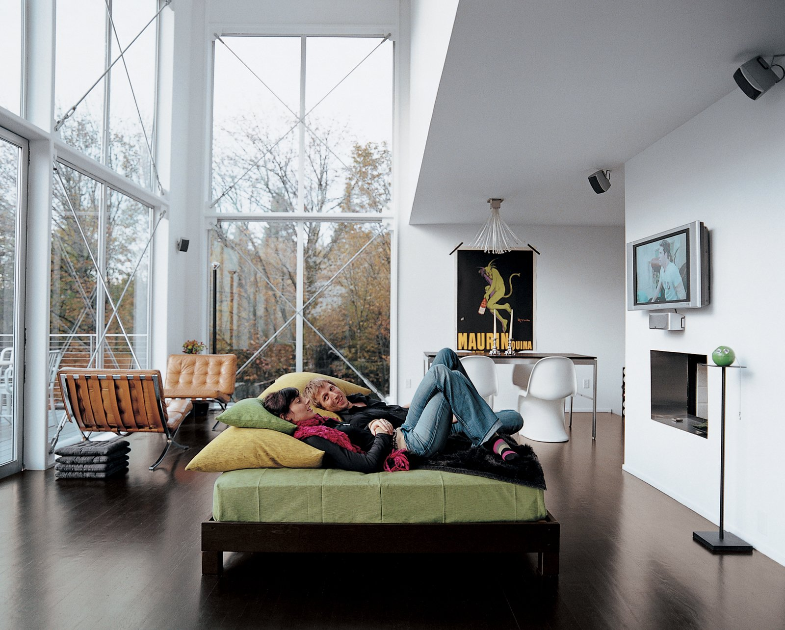 The couple lounges in their great room. The 16-foot-high windows are from Milgard. Aloft in the Forest - Photo 3 of 8