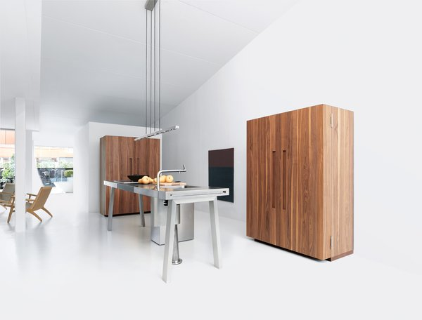 Bulthaup's b2 system comes equipped with everything a kitchen needs—the workbench contains a sink, trash receptacles, and cooktops, while the two wooden cabinets house the appliances and the kitchenware.