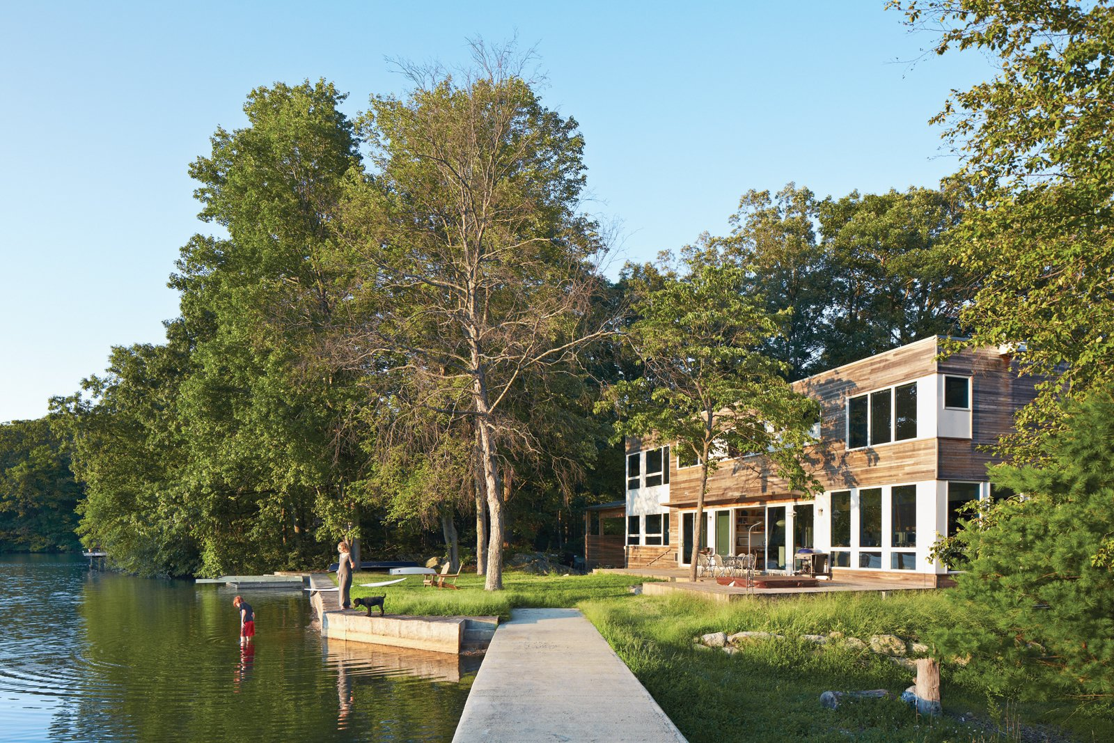 """The house's narrow footprint works for us in terms of maximum exposure to the lake,"" says Gibbs (shown here with son Blake and dog Max on the shore of Lake Iosco). Glass walls and doors by Andersen also mean that Gibbs can keep a close eye on Blake when he's playing in the yard. A plinth of reused bedrock found on the property has become an unintended place for active play. Tagged: Exterior, House, Boathouse Building Type, and Wood Siding Material.  Photo 6 of 9 in The New Zealand Native Who Can't Get Enough of the Garden State"