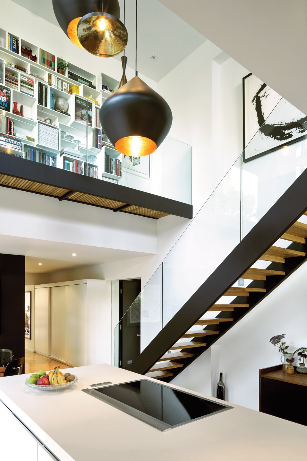 The couple's white Bulthaup kitchen is set within a double-height volume hung with Tom Dixon Beat lights, arranged in a custom configuration by interior designer Maria Rosa Di Ioia. Overhead, Cubit shelving artfully displays books and objects, accessible by a glass-walled footbridge added during the renovation. Tagged: Staircase and Wood Tread.  Renovations by Evander John Torio from A Renovated Flat in Moshe Safdie's Habitat '67
