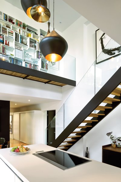 The couple's white Bulthaup kitchen is set within a double-height volume hung with Tom Dixon Beat lights, arranged in a custom configuration by interior designer Maria Rosa Di Ioia. Overhead, Cubit shelving artfully displays books and objects, accessible by a glass-walled footbridge added during the renovation.