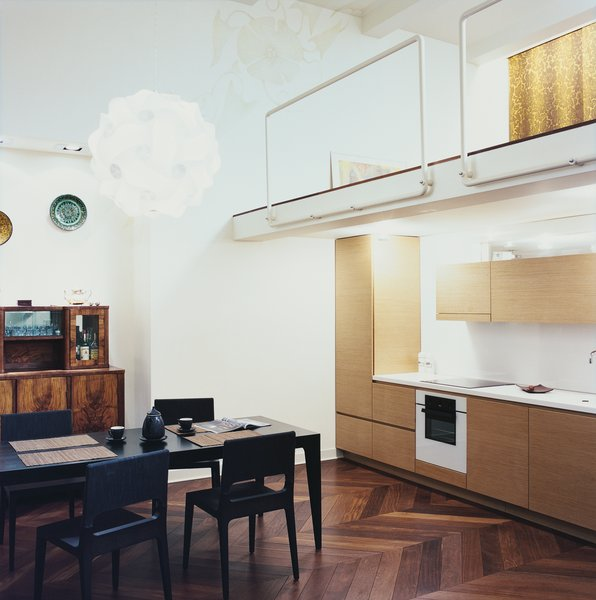 The kitchen fits neatly on one wall. The architect reads at a black Ligne Roset dining set, beneath a Col pendant lamp by Francisco Luján. The tublar steel mezzanine rails were designed by Mikulionis, who enjoyed being exempt from the safety concerns that a client would force on him.