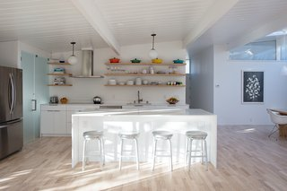 Sunny Renovation of an Eichler Great Room - Photo 2 of 5 - The updated kitchen features a bright white palette. The countertop is Caesarstone's Blizzard surface and the stools are Crate and Barrel. The range hood is Futuro, the refrigerator is LG, and the dishwasher is Bosch.