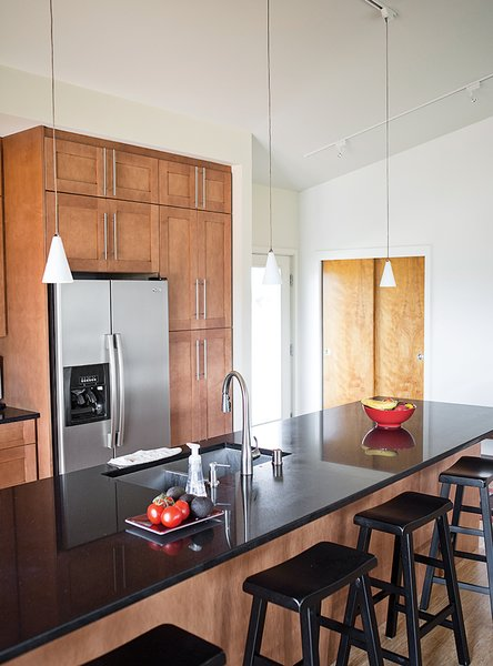 The kitchen island, with a Raven countertop from Caesarstone's Classico Collection, is illuminated by a set of April pendant lamps by WAC Lighting.