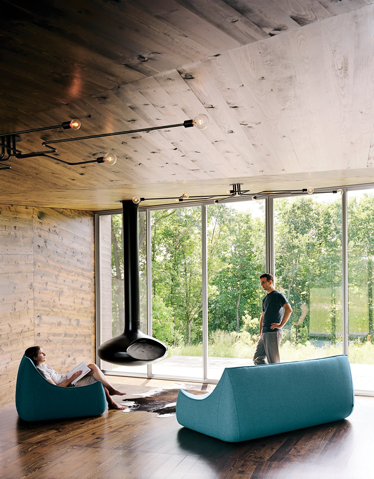 New Grass Roots  With its corrugated-aluminum exterior, X House in Hennepin, Illinois, was built to resemble rural silos. The inside, however, features rich wood paneling and spare furnishings. From floor-to-ceiling windows, the residents have a view of the surrounding grassland.  New Grass Roots by Dwell from Minimalist Living Rooms