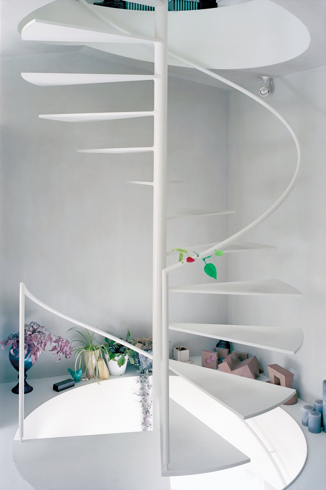 A steel spiral staircase efficiently links all three floors. With no interior doors, Yurika can keep an ear on the shop from upstairs while maintaining the privacy of her home with the help of the vertical distance. Tagged: Staircase, Metal Tread, and Wood Railing.  Photo 8 of 11 in Small Space Live/Work Box Home in Japan