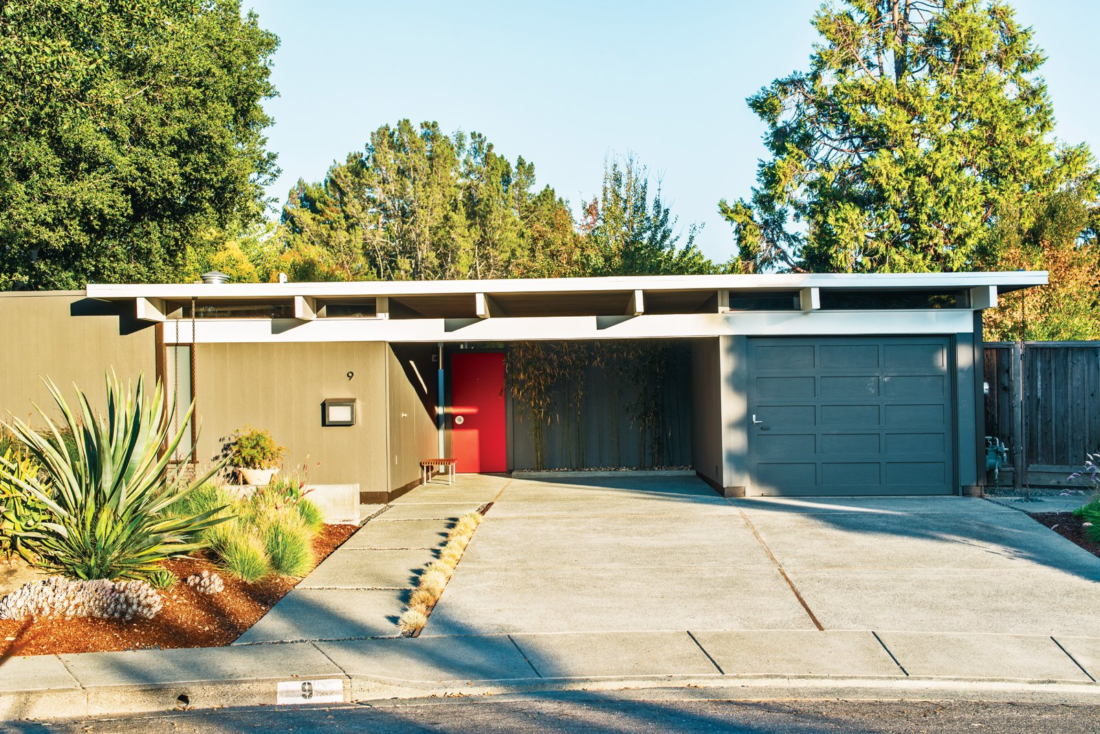 The exterior of Neely and Kefalides's house is punctuated with a bright red door.  Photo 9 of 15 in Modern Furniture Fit for a Classic Eichler