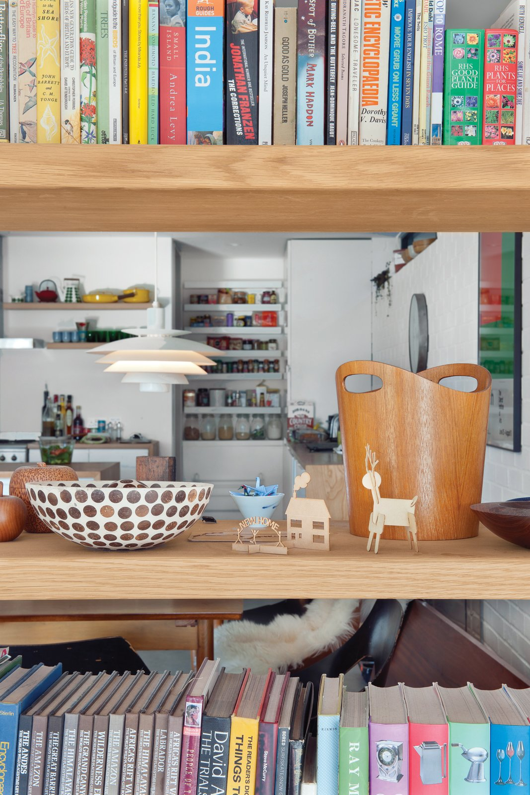 Open shelving between the living room and dining area maximizes light and air flow and showcases eclectic objects, which include old printing blocks found at a garage sale and bowls Tyler's mother bought in South Africa. An Obsessed Designer Fills Her Home with Vintage Finds - Photo 2 of 18