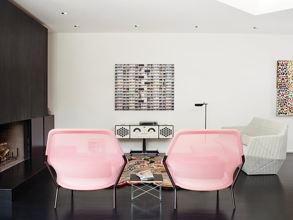 A pair of Slow chairs by the Bouroullec brothers for Vitra frame a new Brionvega RR226 stereo by Achille Castiglioni in the living room. The photograph by Michael Wolf of a Hong Kong apartment building is from a series that ran in the March 2004 issue of Dwell.