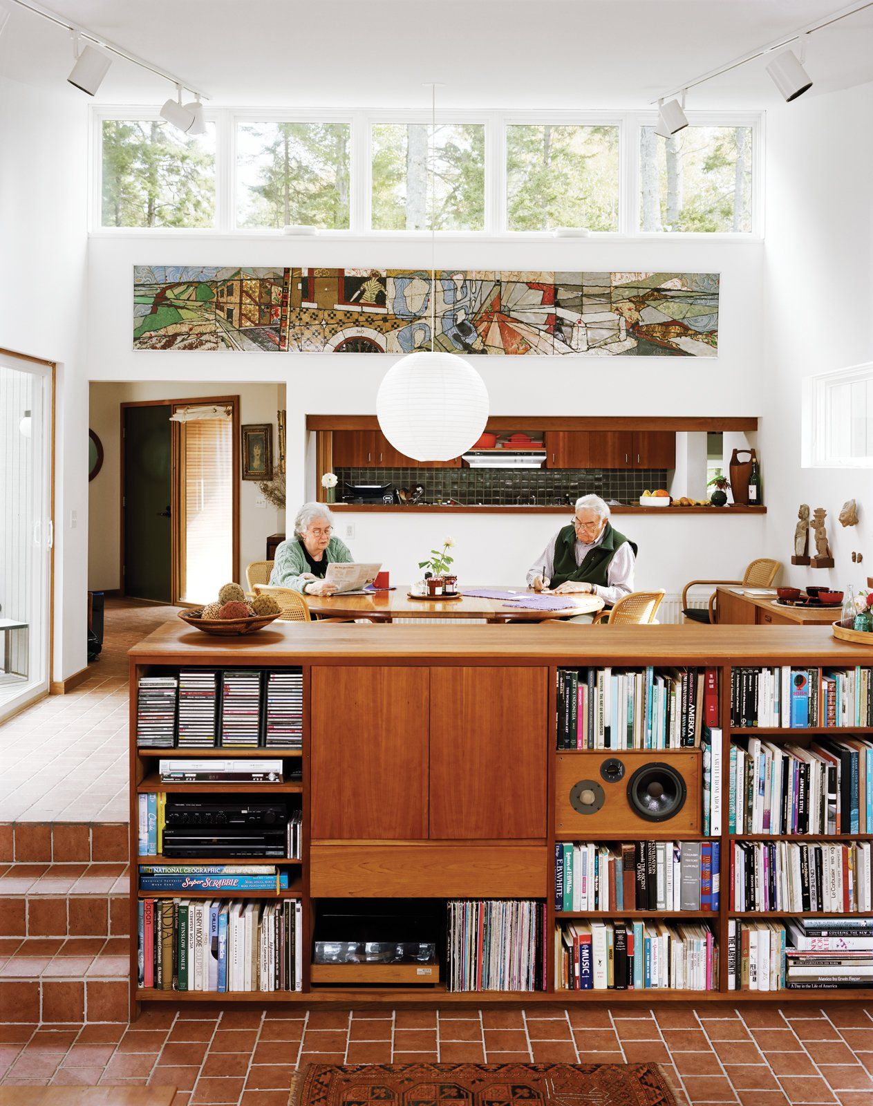 Cohen and his wife, Sally, sit in the dining room, which along with the connected living room, is a focal point of the house, lighted in part by high, remote-controlled clerestory windows. Tagged: Living Room, Shelves, Pendant Lighting, Storage, and Ceramic Tile Floor. The Right Track - Photo 1 of 15
