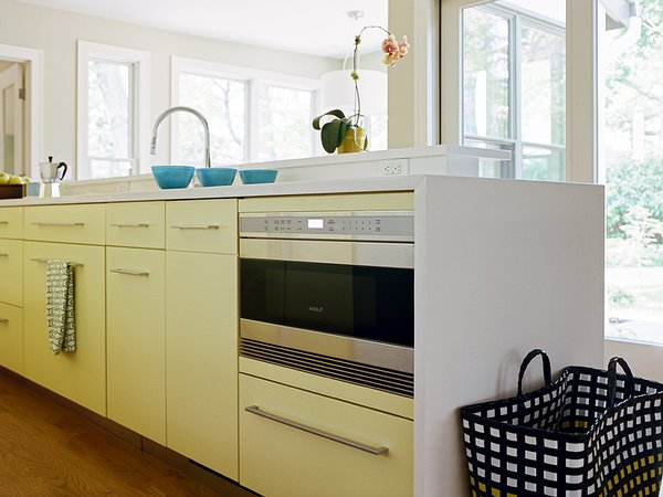 In northern New Jersey, a cramped kitchen is reborn as a welcoming space for cooking and entertaining. Decked out in a subtle yellow, the kitchen houses a Wolf drawer microwave tucked unobtrusively under the counter in the display island.