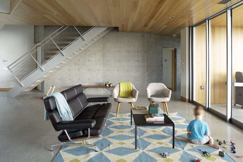 4-year-old Robin plays in the home's great room, which is furnished with original mid-century pieces that belonged to Beck's grandmother, including two Saarinen chairs, a Knoll coffee table, and Bertoia bench.  Photo 4 of 10 in Angular Modern Beach House in Florida