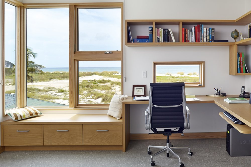 """The guest room doubles as a home office. Here, too, are cypress built-ins framing glass panels that look out onto the sea. The architects call them """"St. Jerome boxes,"""" which is inspired by the classic image of St. Jerome at his desk, lost in thought, with the landscape framed in a picture window beside him."""