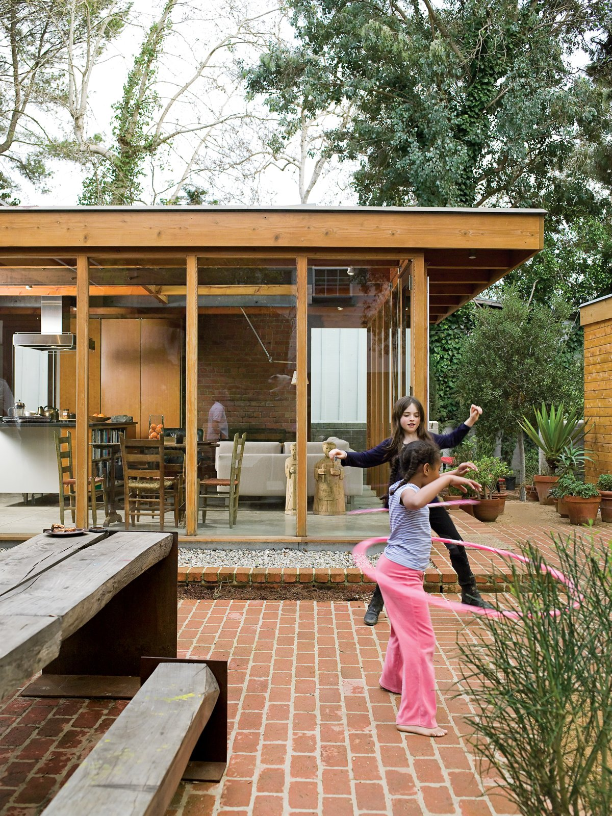 The courtyard acts like an outdoor living room, where the Arnolds' daughter, Josie, plays freely, safe from nearby traffic. The family dines here most of the year at the custom-designed wood-and-steel table. The picnic table set reappropriates the century-old eucalyptus tree that once grew on the site. Tagged: Outdoor, Large Patio, Porch, Deck, and Back Yard.  Photo 9 of 12 in Compound Addition