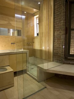 Domestic Ribbon - Photo 8 of 9 - Chan outfitted the bathroom in marine fir plywood from Rosenzweig Lumber for its resistance to high-moisture environments. The fixtures are from Vola; the bathtub, countertop and sinks are of magnesite. The full-height glass is stationary except for a sliding door at left, and a curtain can be rolled down for privacy.