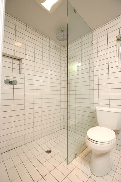 """Popp removed the old bath/shower combo and remodeled the configuration of the shower, which now has one-level access for safety and ease of use, and installed a remote operating device. """"The tile is all Heath seconds,"""" says Popp, who found enough pieces to cover the entire 250-square-foot bathroom."""