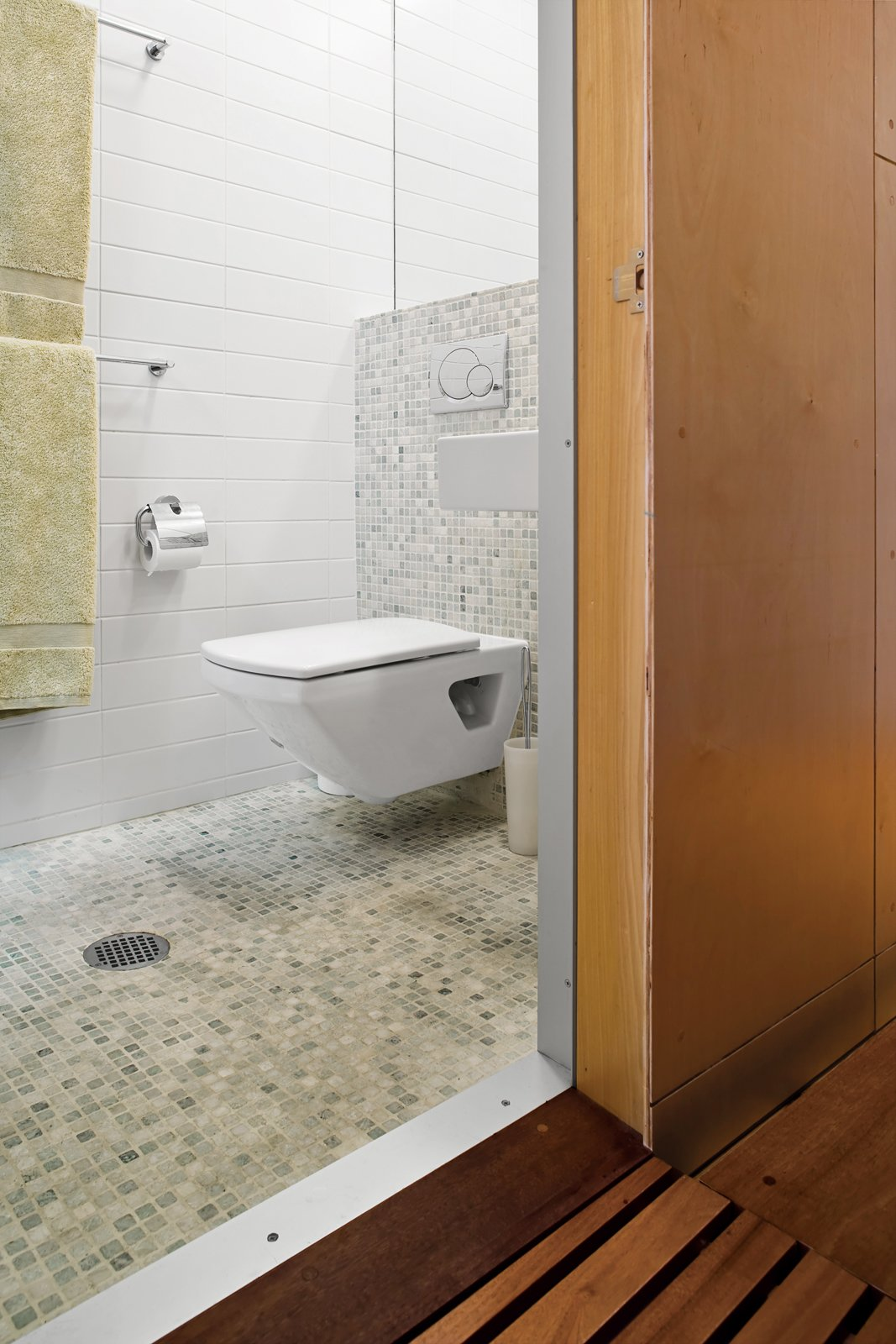 A skylight in the compact bathroom opens the space, and green tiles give the room a spa-like feel. Tips for Tiny Bathrooms - Photo 13 of 13