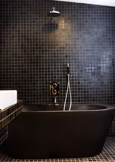 10 Ideas For Designing With a Modern Bathtub - Photo 1 of 10 - Black tiles and fittings lend the bathroom a dramatic look. The black bathtub is made of recycled plastic.