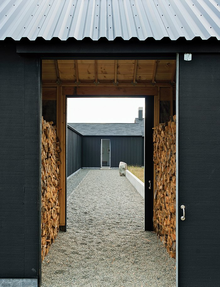 The gravel path leading to the front door passes through firewood storage and the central courtyard. Idyllic Home Designed for an Artist - Photo 2 of 18