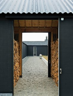 Idyllic Home Designed for an Artist - Photo 2 of 18 - The gravel path leading to the front door passes through firewood storage and the central courtyard.