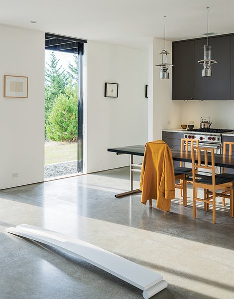 Lanterns from Stelton hang above the dining table and chairs Brothers designed. Nevamar laminate covers the kitchen cabinets, which feature pulls from Häfele. The range is by Wolf.