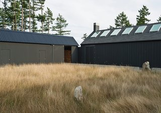 Idyllic Home Designed for an Artist - Photo 12 of 18 - Linden specified a black stain from Cabot for the house's exterior. The shade draws on Scandinavian and Japanese building traditions and helps the structure blend into the landscape. Native grasses populate the courtyard.