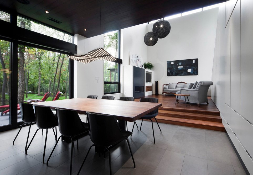 A Rhythm Horizontal lamp by Arik Levy for Vibia hangs above the dining table in a house that Blouin Tardif Architecture-Environnement designed for a family in Boucherville, Quebec, near Montreal.  Photo 1 of 7 in Near Montreal, a House Connects With Its Surroundings