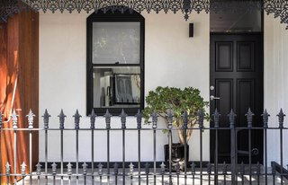 Renovated 19th-Century Terrace House Merges with the Outdoors - Photo 1 of 7 - The home's white stucco walls and chestnut-hued timber offer a modern contrast to its filigree railing and ornamentation.