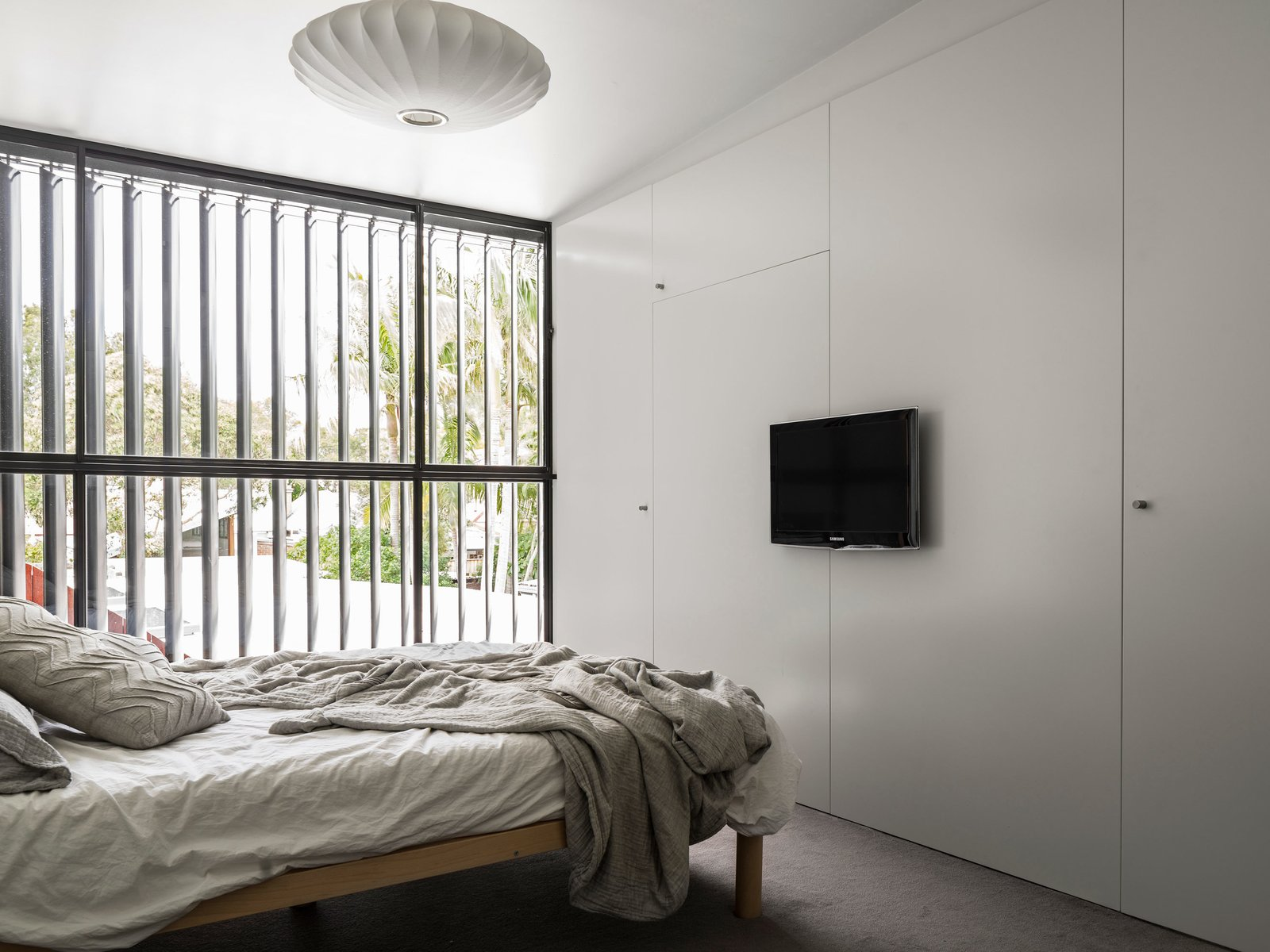 Full height louvers are used throughout the house, opening the interior spaces up to the outdoors. Tagged: Bedroom, Bed, Pendant Lighting, and Carpet Floor. 5 Energy-Efficient and Stylish Ways to Shade Your Windows - Photo 6 of 16
