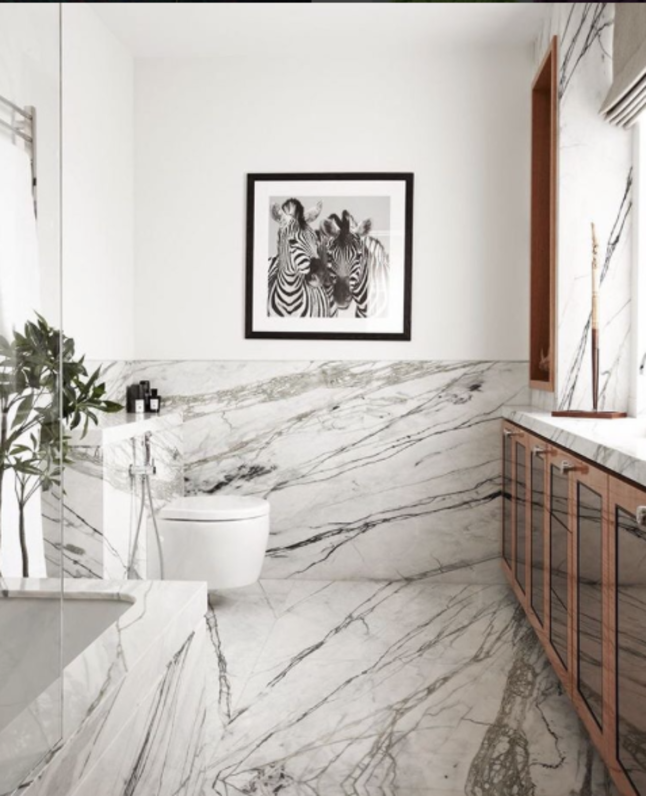 In this picture from @_decoh, the veiny marble is explicitly referenced by hung photograph.  Bathroom by Isabelle Perfetto from Spotted on Instagram: Five Totally Different Styles for Your Bathroom