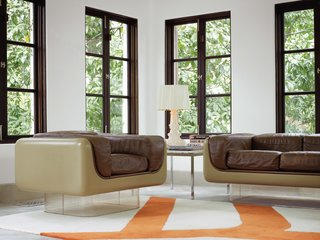 A Designer Brings Her Bold Brand of Texas Modern to this Atlanta Family Home - Photo 2 of 9 - To highlight the existing architecture of the home, Hill retained the dark polish of the casement windows, which she finds enhances period details instead of undermining them. In the rear sunroom, the vintage Case Study furniture pieces with Plexiglas bases are from Metro Retro in Houston.<br><br>A Bourgie lamp by Kartell is atop an old marble end table by Knoll, and the Gan kilim rug pictures a branch motif echoed in the kitchen and breakfast room.