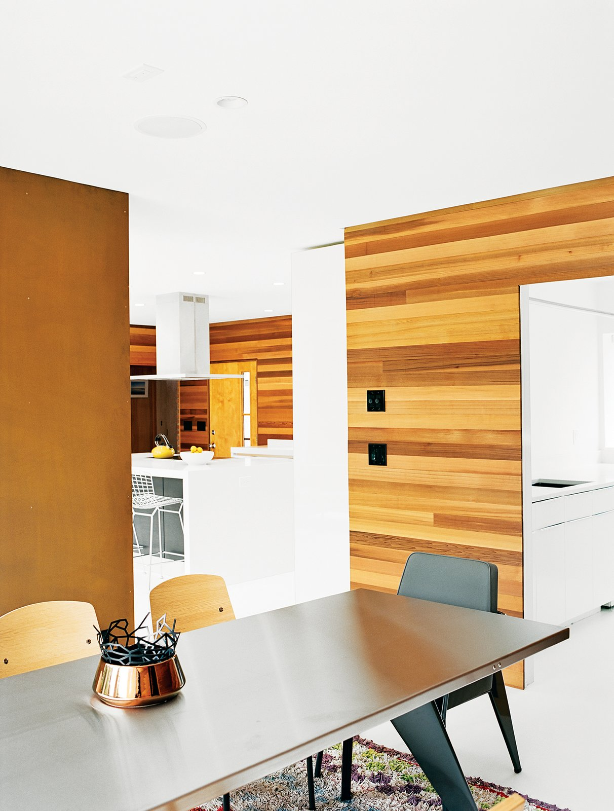 Jordan removed built-in shelving behind the stone fireplace and installed a Cor-Ten steel panel in its place. Vitra manufactures the Jean Prouvé–designed Standard dining table and side chairs. Tagged: Dining Room, Chair, and Table.  Photo 2 of 12 in The Midcentury Spirit is Alive and Well in This Hudson Valley Escape